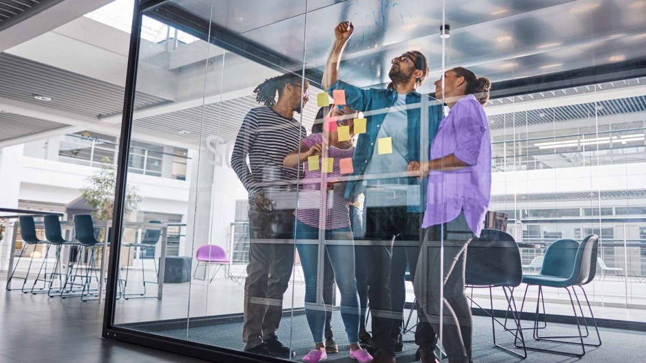 Image of team collaborating in glass office