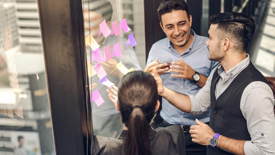 Image of 3 people with post-it notes on window